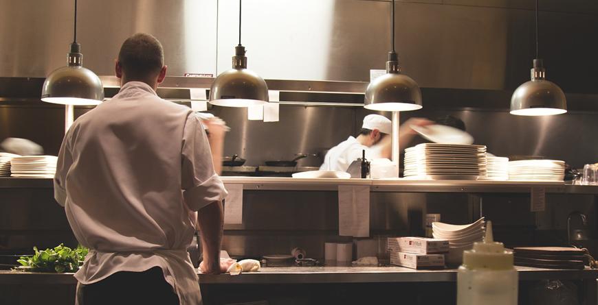 cocina de restaurante con un cocinero de espaldas y otro en frente cogiendo un plato